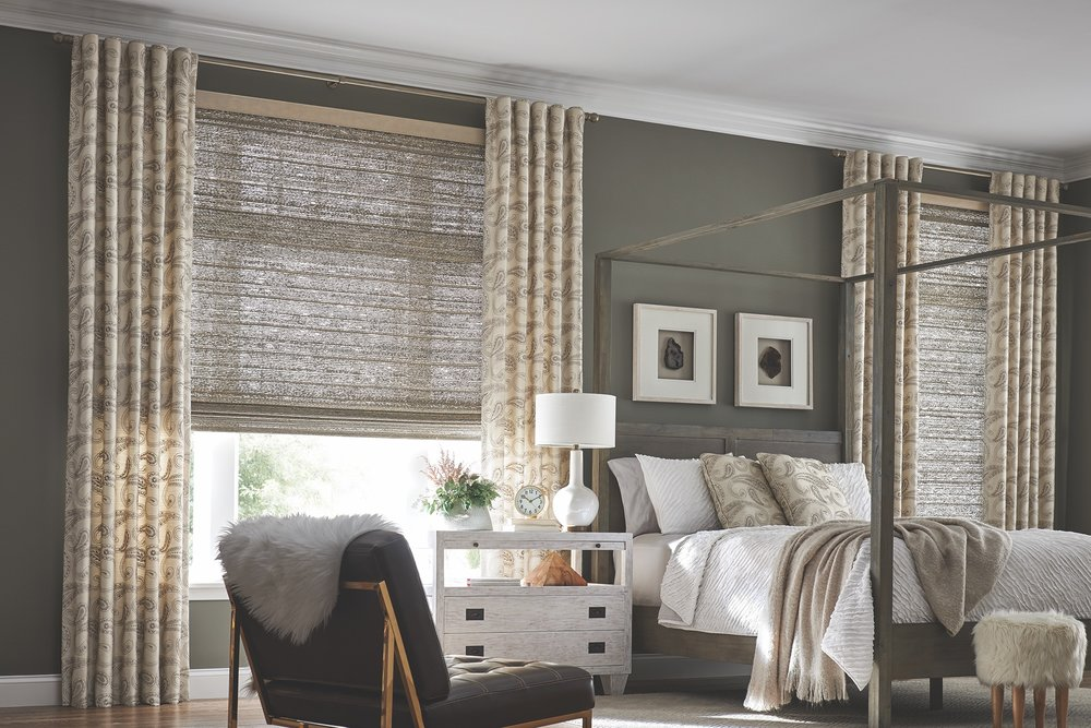 Natural woven shades paired with drapes in a primary bedroom