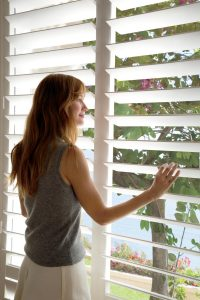 Woman looking out window through shutters